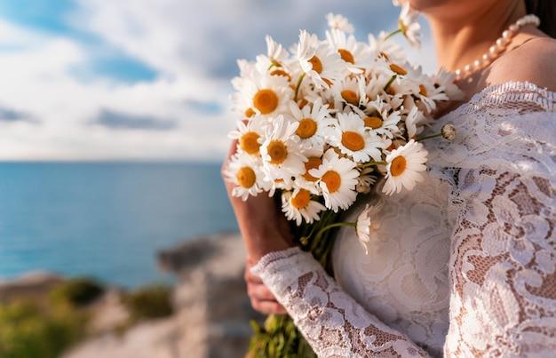 하얀 드레스를 입고 신부 손에 필드 데이지의 여름 꽃다발. 바다의 배경에 따뜻한 일몰 시간. 공간을 복사하십시오. 평온함, 침묵, 자연과의 단결의 개념. 프리미엄 사진