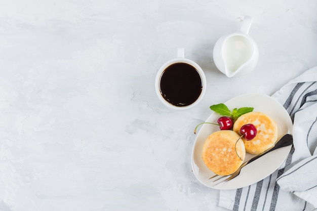 Summer breakfast with cottage cheese pancakes, cup of black coffee, milk Premium Photo