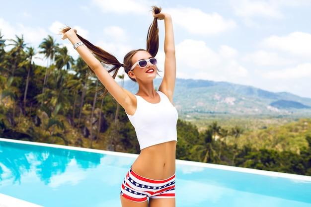Летний яркий портрет сексуальной хипстерской девушки, развлекающейся на вечеринке у бассейна, держа ее за хвостики и флирта, радости, отпуска, тропического острова. Бесплатные Фотографии