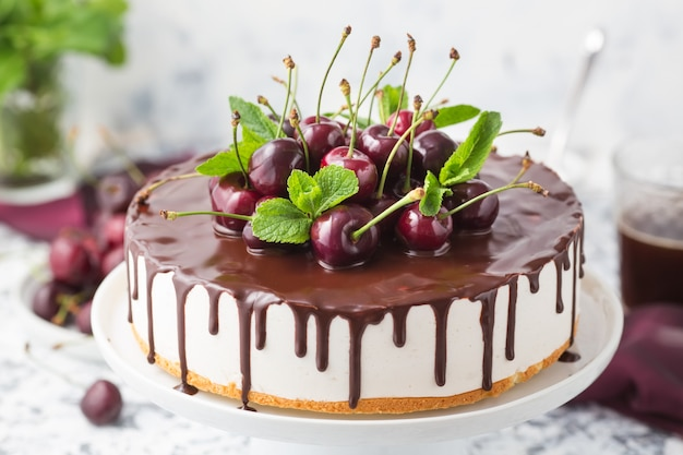 Summer cake with chocolate topping decorated fresh cherries on a white cake stand Premium Photo