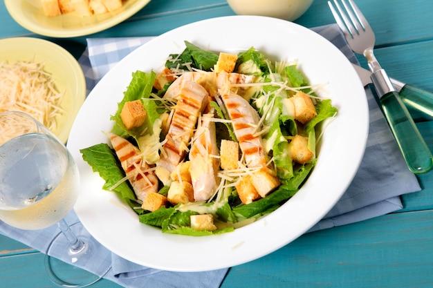 Summer chicken caesar salad on picnic table Free Photo