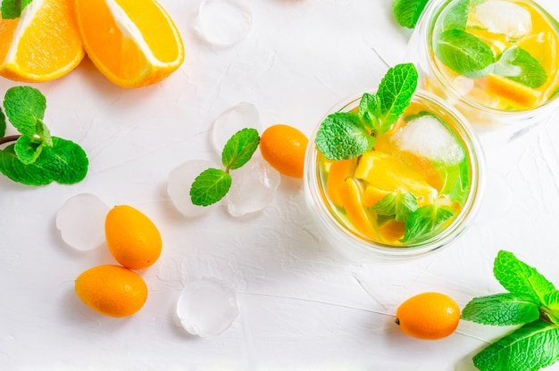 Summer citrus drink with orange, kumquat, mint and ice cubes on white background. flat-lay, top view. Premium Photo