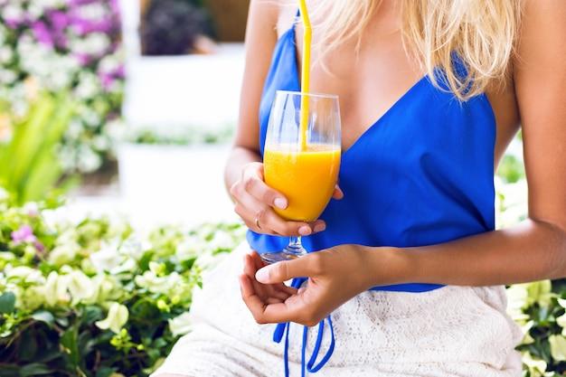 Лето крупным планом изображение женщины, держащей свежий органический вкусный смузи из манго Бесплатные Фотографии