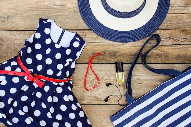 Summer clothing and accessories: dress, purse, hat, headphones, perfume, handbag and beads on old wooden background. Premium Photo
