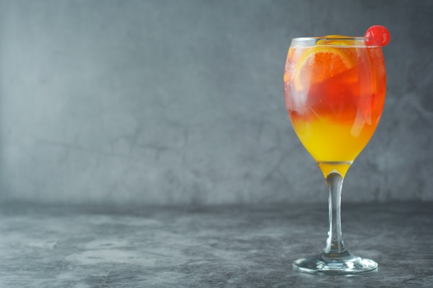Summer cocktail. orange juice with mint, syrop, fruit slices and cherry with ice. Premium Photo