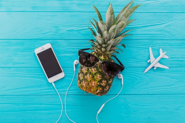 Summer composition with pineapple, sunglasses and mobile phone Free Photo