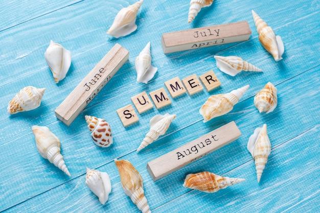 Летняя композиция с морскими раковинами и деревянными блоками Бесплатные Фотографии