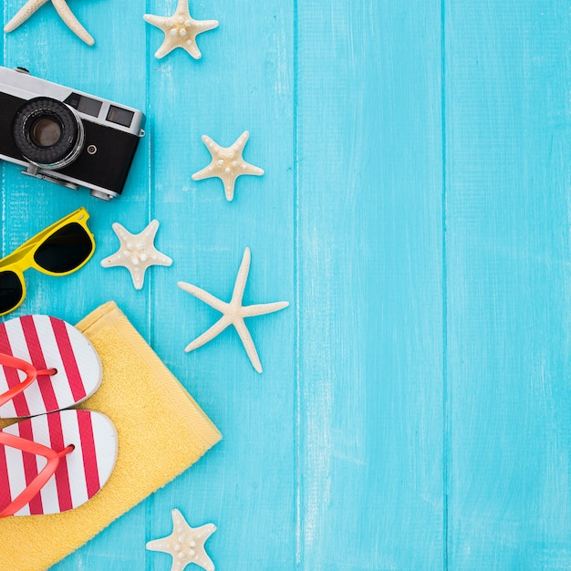 Summer concept with vintage camera, sunglasses, towel, starfish on blue wooden background Free Photo