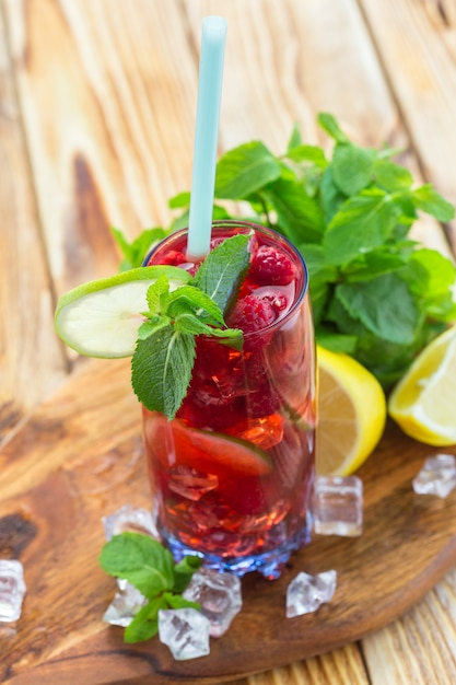 Summer drink with raspberries, lime and ice on a old wooden table Premium Photo