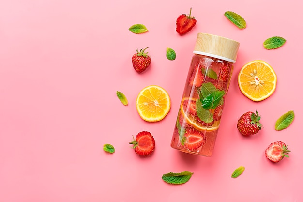 Summer drink with strawberry, lemon, leaf of mint on pink background. Premium Photo