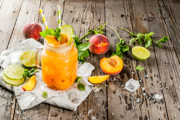 Summer drinks, cocktails. vegan food. peach smoothies, juice or lemonade. in a mason jar, with lime Premium Photo