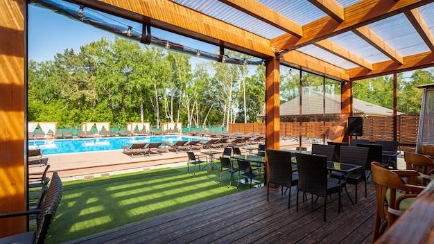 Летнее пустое уличное кафе в парке. бар-кафе с современным дизайном, деревянные стены, стулья, столы Premium Фотографии