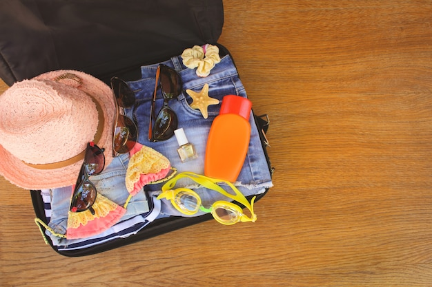 Summer family things and accessories in suitcase. toned image. top view. Premium Photo