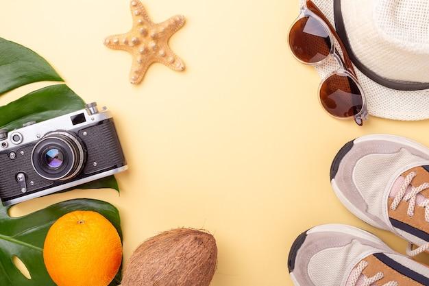 Летняя мода плоская планировка. ветки монстеры, солнцезащитные очки, кроссовки, шляпа и ретро-камера Premium Фотографии
