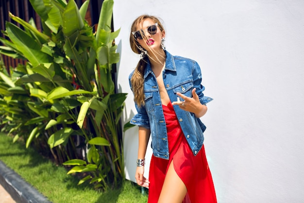 여름 패션 초상화 O 멋진 우아한 패션 소녀가 열대 지방에서 포즈를 취하고 우아한 럭셔리 드레스와 트렌디 한 데님 재킷을 입고 춤을 추고 재미를 보았습니다. 무료 사진
