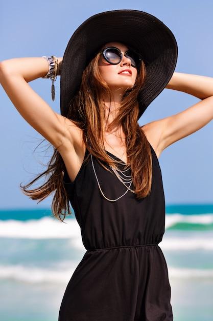 아름 다운 여자의 여름 패션 초상화는 바다, 휴가 스타일 근처 바람이 부는 화창한 날을 즐길 수 있습니다. 검은 장난 꾸러기 빈티지 모자와 큰 선글라스, 밝은 색상, 자유, 행복을 입고 세련된 소녀 무료 사진