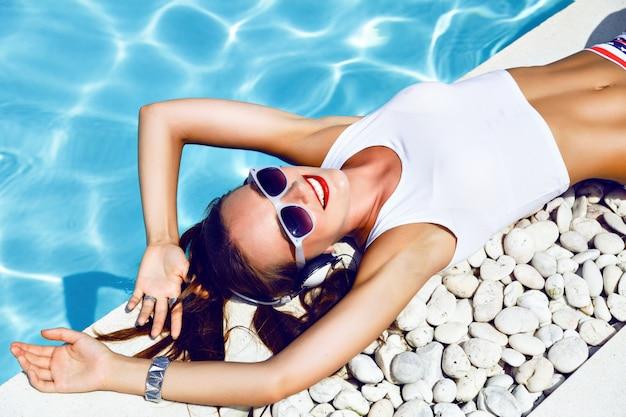 Ritratto di moda estate di giovane ragazza dj sexy posa vicino alla piscina, indossando mini shorts sexy con occhiali da sole vintage stelle, acconciatura carina e trucco luminoso, ascoltando musica in cuffia. Foto Gratuite