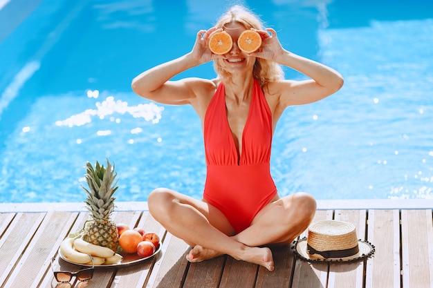Moda estiva. donna in costume da bagno rosso vicino alla piscina. signora con la frutta. Foto Gratuite
