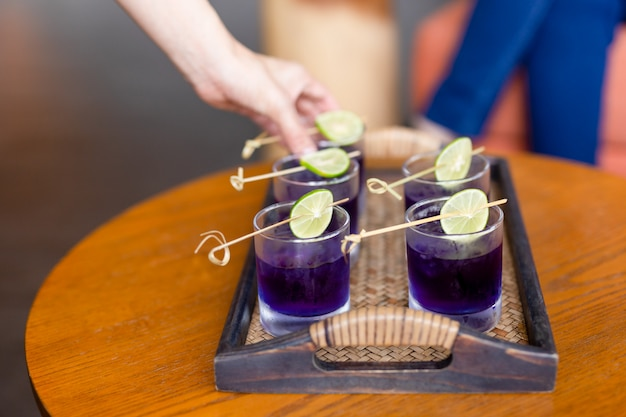 Summer fresh drink butterfly pea drink and slice of lime on a bamboo tray. Premium Photo
