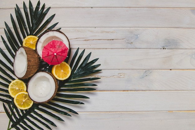 Summer fruits and palm leaves on wooden surface Free Photo