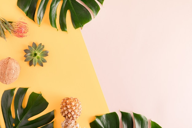 Summer fruits and leaves. tropical palm leaves, pineapple, coconut on pastel yellow and pink background. flat lay, top view, copy space Premium Photo