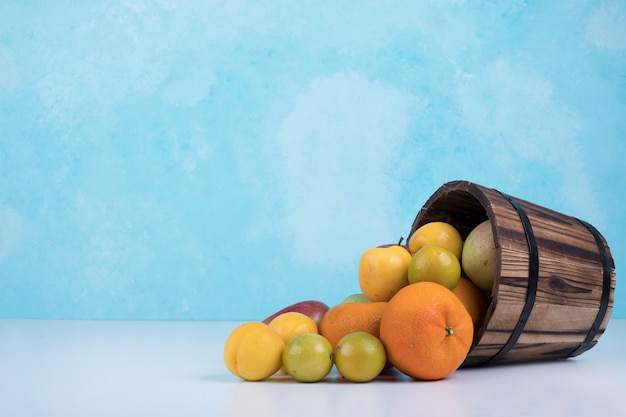 Summer fruits mix out of a wooden bucket on blue. Free Photo