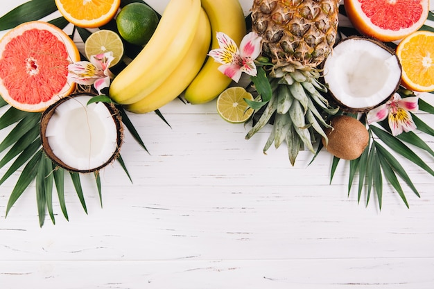 Summer fruits. tropical palm leaves, pineapple, coconut, grapefruit, orange and bananas on wooden background. Premium Photo