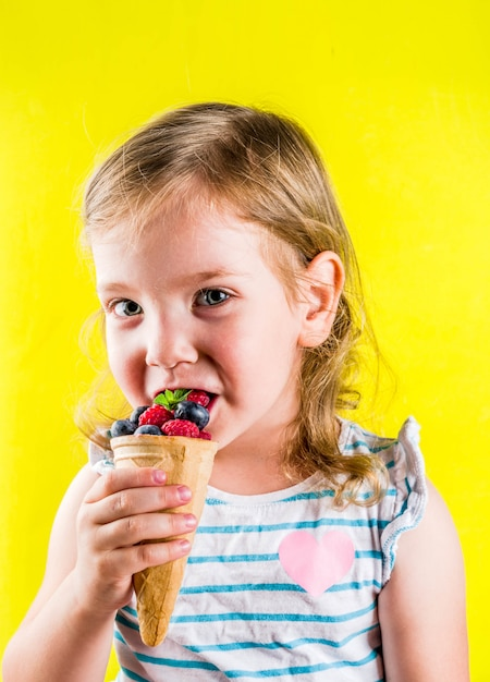 Summer fun holiday concept, cute blonde toddler girl eating berries from waffle ice cream cone, bright yellow  background Premium Photo