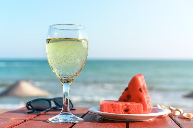 Summer, a glass of champagne and fruit against the background of the sea Premium Photo