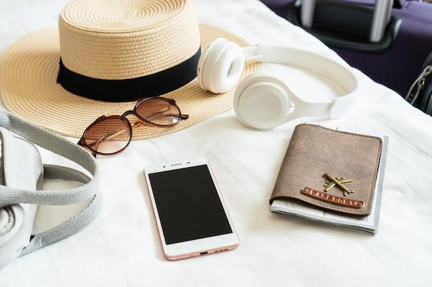 夏の帽子サングラスバッグヘッドフォンパスポートとモダンなホテルの部屋のベッドで女性旅行者のスマートフォン旅行リラクゼーション旅行旅行と休暇の概念クローズアップしてスペースをコピーする Premium写真