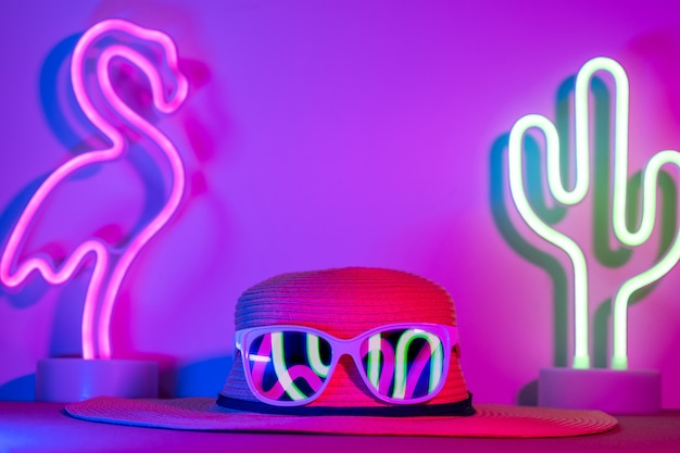 Summer hat with sunglasses refection flamingo and cactus neon pink and blue and green light on table Premium Photo