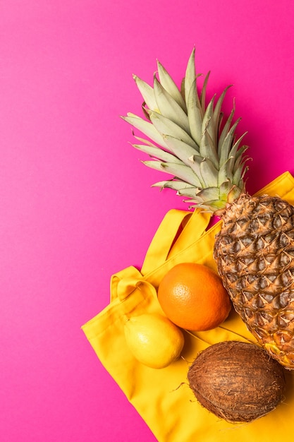 Summer, holiday concept. tropical fruits with a yellow cotton bag on a pink background Premium Photo