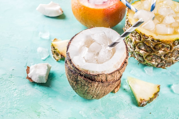 Summer holiday drink concept, set various tropical cocktails or juices in pineapple, grapefruit and coconut with ice, light blue concrete Premium Photo