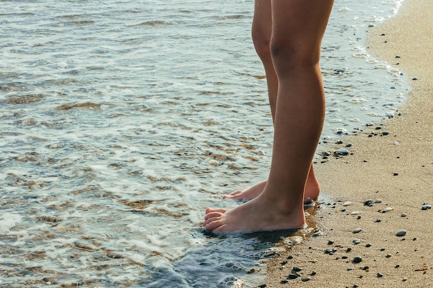 Summer holidays. vacation concept. little boy standing on the beach in water. bare feet. Premium Photo