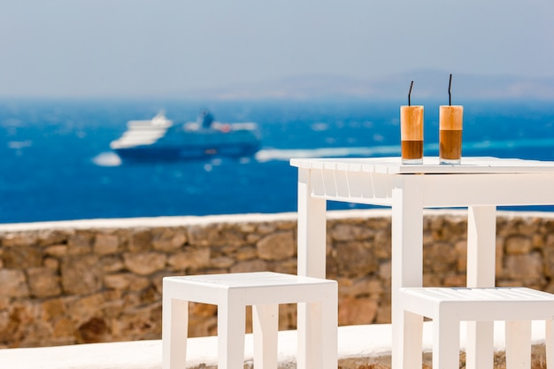 Summer iced coffee frappuccino, frappe or latte in a tall glass in beach bar Premium Photo