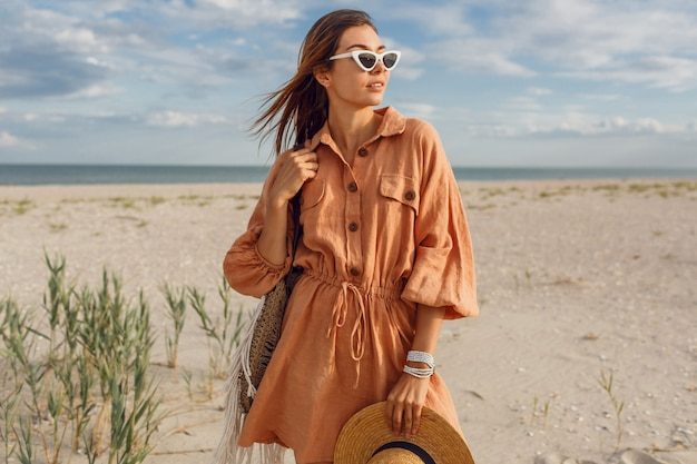 Immagine estiva di bella donna castana in abito di lino alla moda, che tiene il sacchetto di paglia. ragazza abbastanza magra che gode dei fine settimana vicino all'oceano. Foto Gratuite
