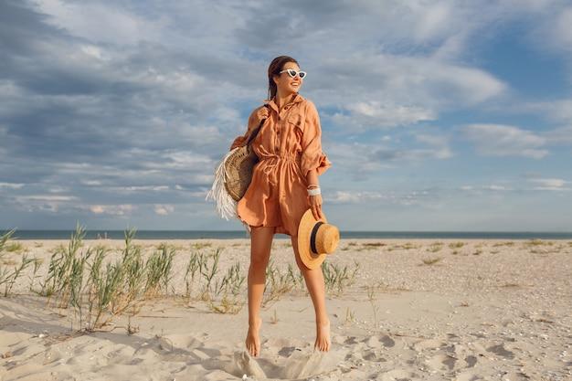 Immagine estiva di bella donna bruna in abito di lino alla moda che salta e scherza, tenendo il sacchetto di paglia. ragazza abbastanza magra che gode dei fine settimana vicino all'oceano. lunghezza intera. Foto Gratuite