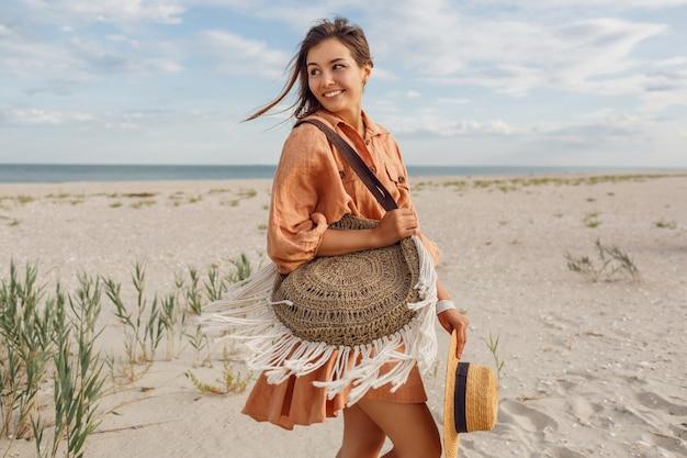 Immagine estiva di bella donna bruna in abito di lino alla moda che salta e scherza, tenendo il sacchetto di paglia. ragazza abbastanza magra che gode dei fine settimana vicino all'oceano. Foto Gratuite
