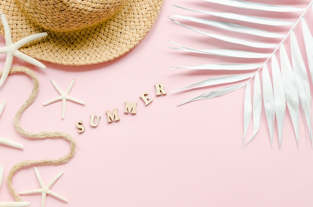 Summer inscription with straw hat and palm leaf Free Photo