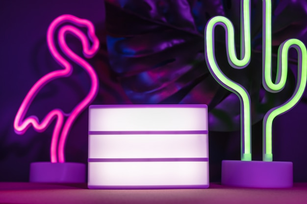 Summer items with flamingo and cactus and blank light box with neon pink and blue light on table Premium Photo