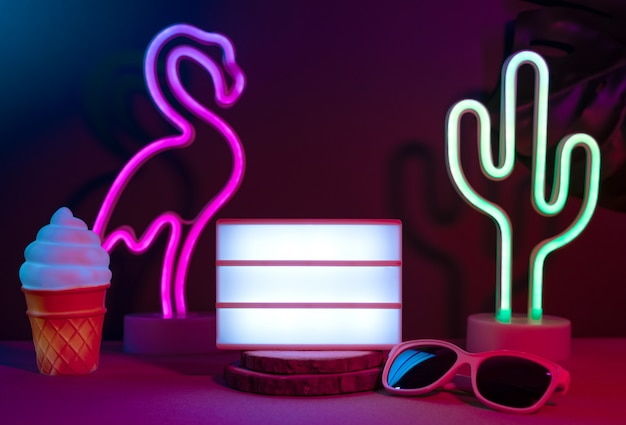 Summer items with flamingo, cactus, sunglasses and blank light box with neon pink and blue light on table with monstera leaf Premium Photo