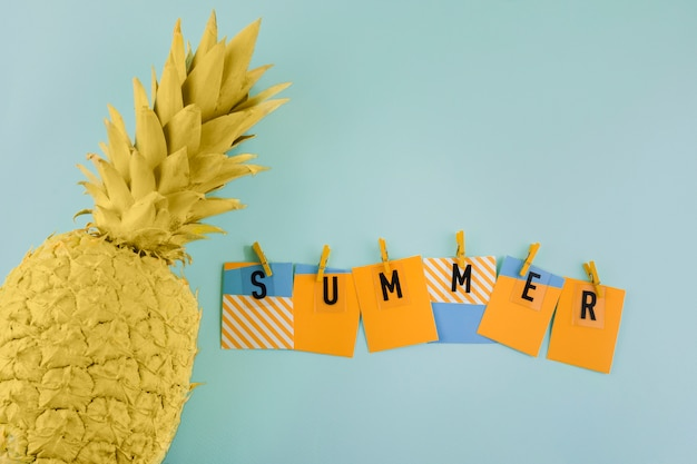 Summer label with clothespin near the painted yellow pineapple on blue background Free Photo