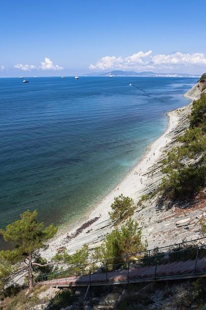 夏の風景岩の上の海への階段は野生のビーチに通じています Premium写真