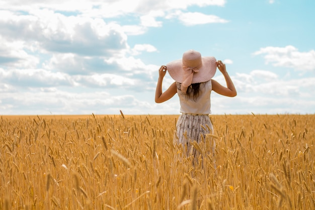 Summer landscape of a wheat field of golden color and blue sky. a women stands in a straw hat and a summer dress looks in the horizon. Premium Photo