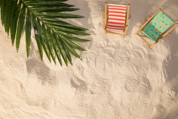 Summer layout of palm tree leaf and small deckchairs on and Free Photo