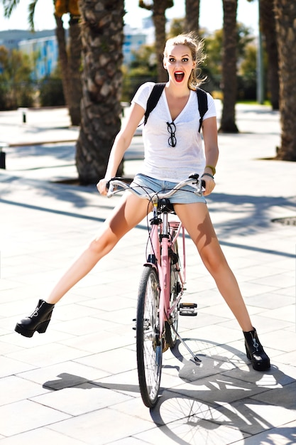 Ritratto di stile di vita estivo di ragazza hipster bionda gioiosa felice, giorni sportivi in forma, andare in bicicletta vintage rosa, viaggiare con lo zaino in paesi esotici, divertirsi all'aperto, palme, parco, natura. Foto Gratuite