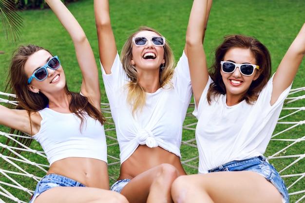 미쳐 가고, 비명을 지르고, 재미를 함께 웃고, 해먹에서 점프하는 나무 여성의 여름 라이프 스타일 초상화. 파티, 기쁨, 재미를 위해 준비된 흰색상의와 선글라스를 착용합니다. 무료 사진