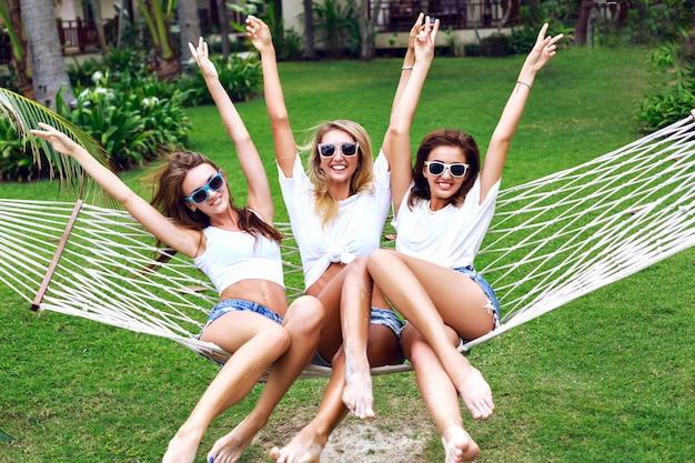 Ritratto di stile di vita estivo delle donne dell'albero che impazziscono, urlano, ridono divertendosi insieme, saltando sull'amaca. indossa top bianchi e occhiali da sole, pronti per la festa, la gioia, il divertimento. Foto Gratuite