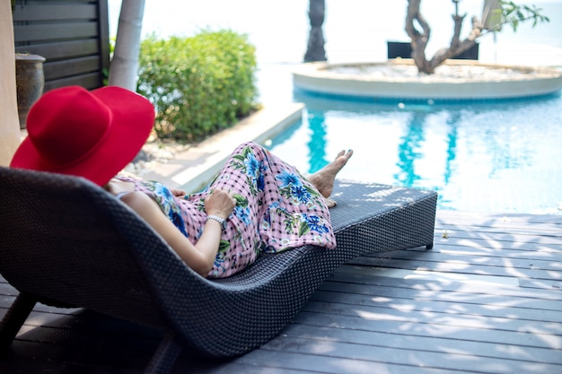 Summer lifestyle woman with red hat lay on sunbed near swimming pool. Premium Photo