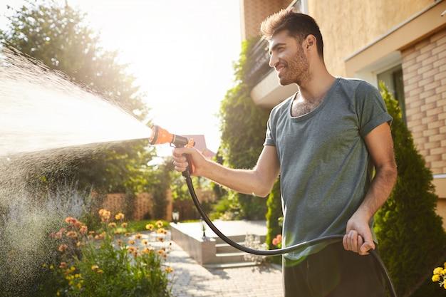 Mattina d'estate in casa di campagna. ritratto di giovane uomo barbuto dalla pelle abbronzata attraente in maglietta blu sorridente, innaffiare le piante con tubo flessibile, lavorando in giardino. Foto Gratuite